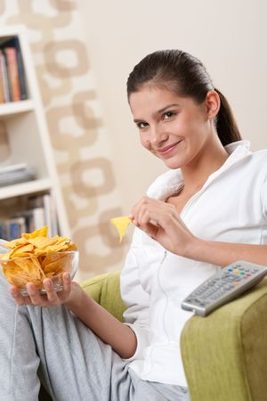 Students - Happy female teenager with potato chips  in modern living room photo