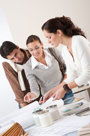 female architect: Female interior designer with two clients at office choosing colors