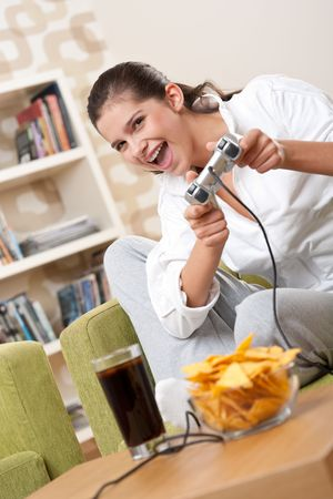 Students - Female teenager playing video game holding game pad in living room photo