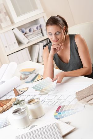 paint swatch: Female interior designer working at office with color swatch choosing color
