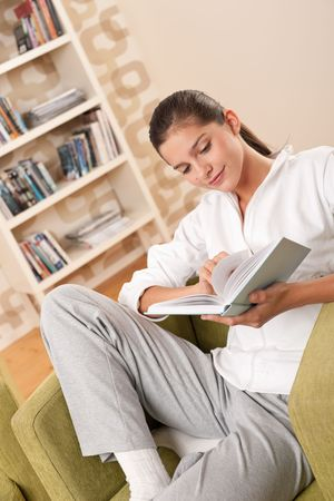 Students - Female teenager reading book in modern living room photo