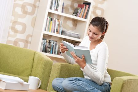 Students - Happy teenager with book sitting on armchair in lounge photo