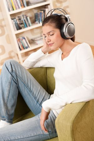 Students - Happy female teenager with headphones listening to music in modern lounge photo