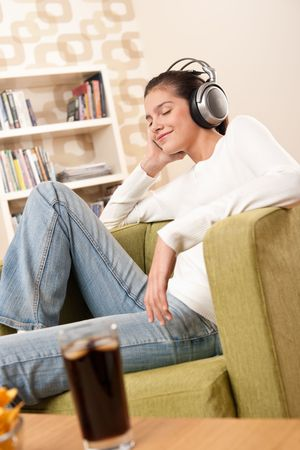 Students - Happy female teenager with headphones listening to music in modern lounge Stock Photo - 5996519