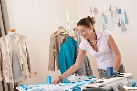 textile designer: Female fashion designer working at studio with pattern cuttings and sketches