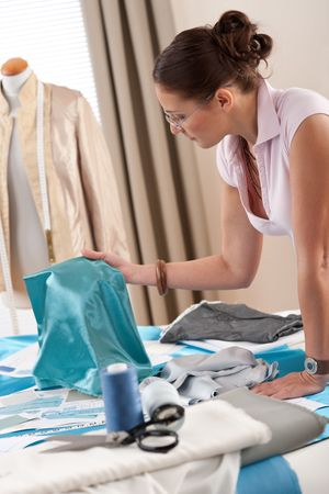Female fashion designer working at studio with pattern cuttings and sketches Stock Photo - 6016439
