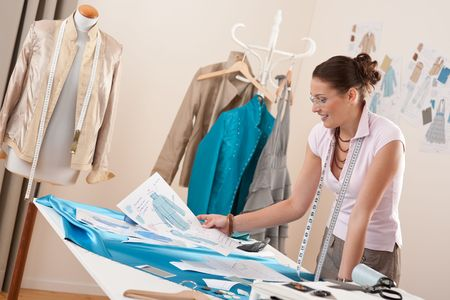 Professional tailor working with fashion sketches at studio photo