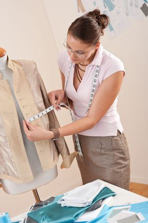 tailor measure: Designer di moda femminile prendendo la misurazione della giacca in studio