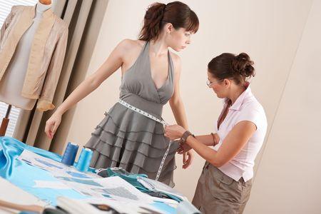 designer clothes: Female fashion designer measuring model for fitting gray dress, taking measurement