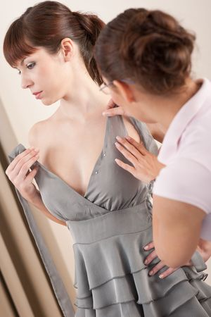 pinning: Female fashion designer pinning gray dress on professional model