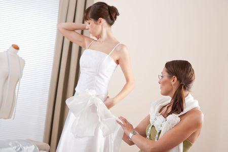 customer tailor: Fashion model fitting white wedding dress in professional fashion designer studio