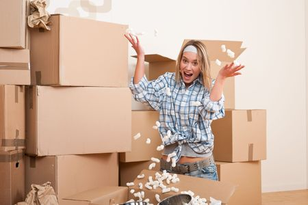Moving house: Young woman having fun unpacking box Stock Photo - 6016458