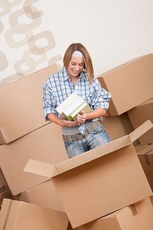 Moving house: Woman unpacking box with book in new home photo