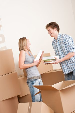 New house: Young couple with box in new home unpacking book Stock Photo - 6016435