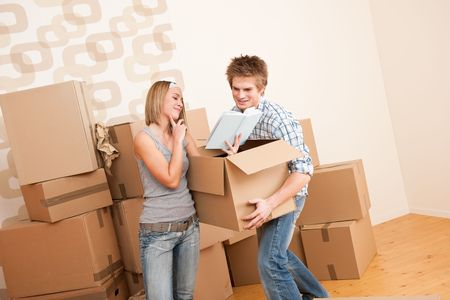 Moving house: Young couple with box in new home, unpacking box Stock Photo - 6016450