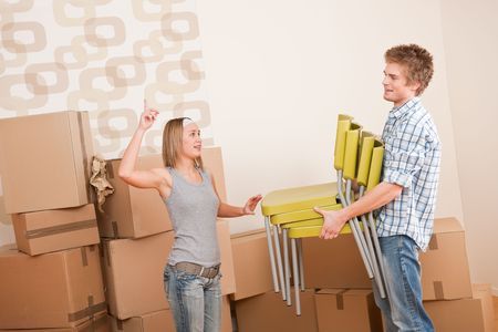 Moving house: Man and woman with box and chair, woman pointing Stock Photo - 6016447
