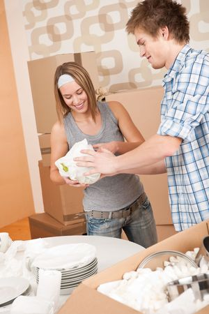 Moving house: Young couple unpacking kitchen dishes, pots, pans, in new home Stock Photo - 6016448