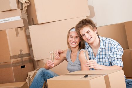 Moving house: Happy couple celebrating with glass of champgne new home Stock Photo - 6016449