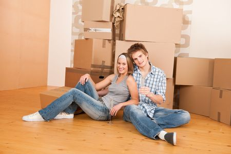 Moving house: Happy couple celebrating with glass of champgne new home Stock Photo - 6016438