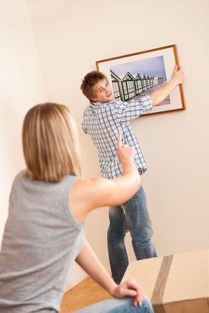 Moving house: Couple hanging picture on wall in new home Stock Photo - 6016455