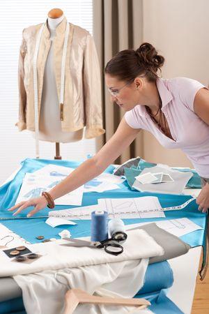 tijeras cortando: Dise�ador de moda femenina trabaja en el estudio con el patr�n de esquejes y bocetos