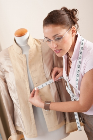 Female fashion designer taking measurement of jacket at studio photo