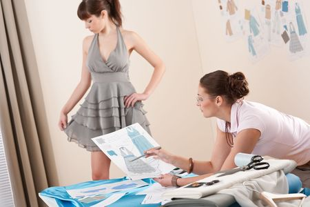 fitting in: Model in gray dress fitting by female fashion designer studio Stock Photo
