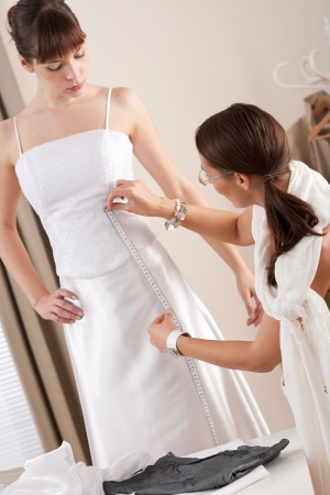 Fashion model fitting white wedding dress in professional fashion designer studio photo
