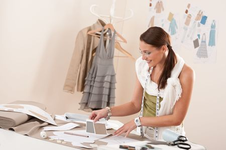 Female fashion designer working with sketches at studio and choosing cloth Stock Photo - 6037653