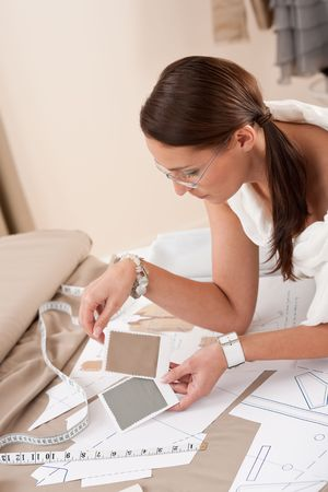 Female fashion designer working with sketches at studio and choosing cloth photo
