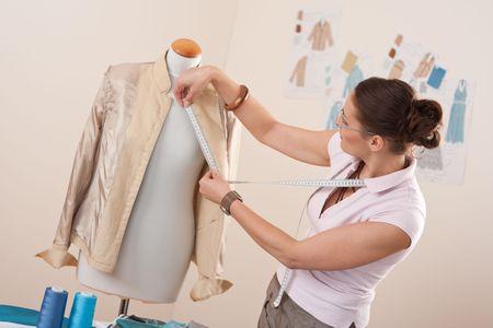Female fashion designer taking measurement of jacket at studio