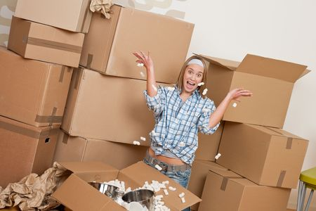 cardboard house: Moving house: Happy woman unpacking box in new home, kitchen, pots and pans Stock Photo