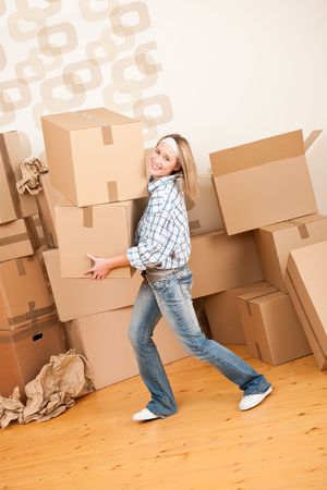 Moving house: Woman holding big carton box in new home