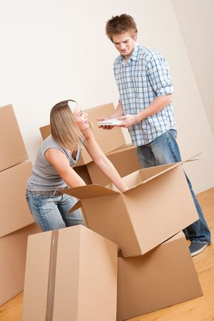 New house: Young couple with box in new home unpacking book Stock Photo - 6048993