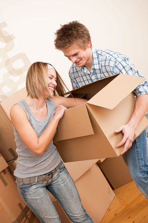New house: Young couple moving box, unpacking in new home Stock Photo - 6048995