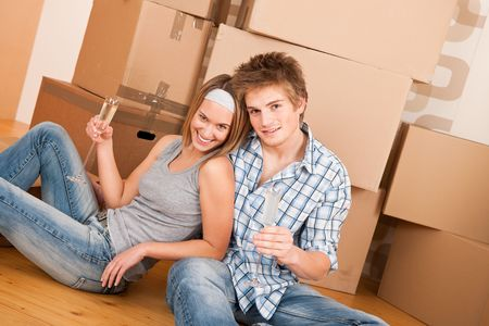 alcohol cardboard: Moving house: Happy couple celebrating with glass of champagne new home