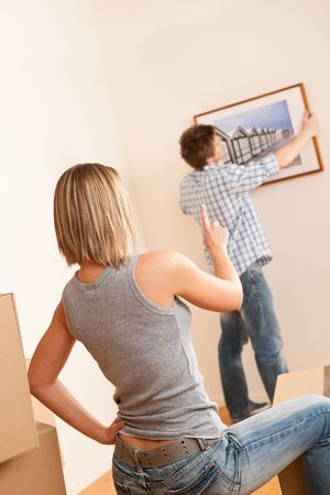 picture person: Moving house: Couple hanging picture on wall in new home Stock Photo