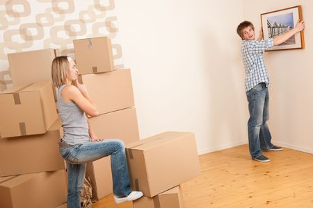 Moving house: Couple hanging picture on wall in new home Stock Photo - 7168095