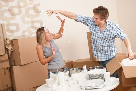 to unpack: Moving house: Man and woman having fun while unpacking box with kitchen dishes