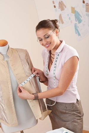 Female fashion designer taking measurement of jacket at studio Stock Photo - 6066698