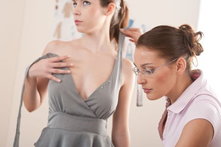 Female fashion designer pinning gray dress on model photo