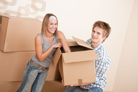 New house: Young couple moving box, unpacking in new home Stock Photo - 6092354