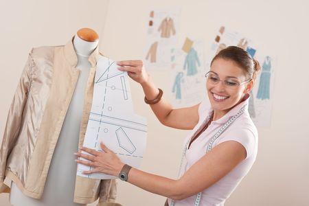 textile designer: Female fashion designer working with pattern cutting at studio Stock Photo