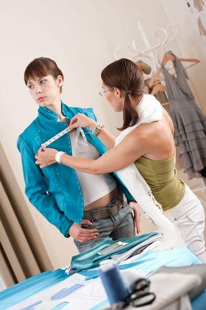 customer tailor: Female fashion designer measuring turquoise jacket on model, taking measurements Stock Photo