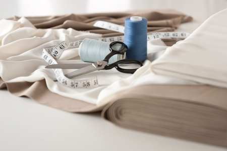 Fashion designer studio with professional equipment on desk, cloth, scissors