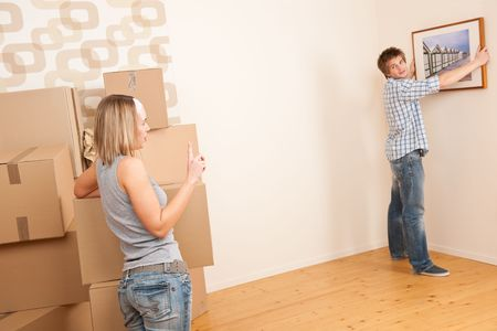 Moving house: Couple hanging picture on wall in new home Stock Photo - 6106918