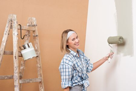 Home improvement: Happy woman painting wall with paint roller photo