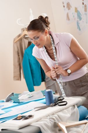 Female fashion designer working at studio with pattern cuttings and sketches Stock Photo - 6106913