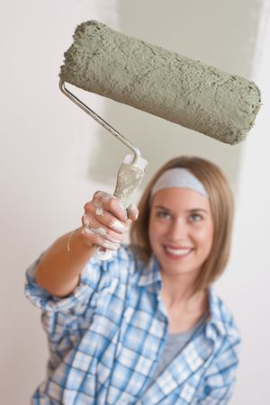 Home improvement: Smiling woman with paint roller painting wall photo