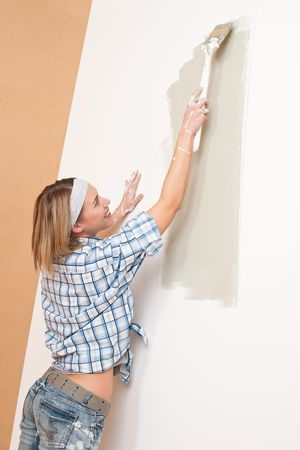 Home improvement: Smiling woman with paint brush painting wall photo